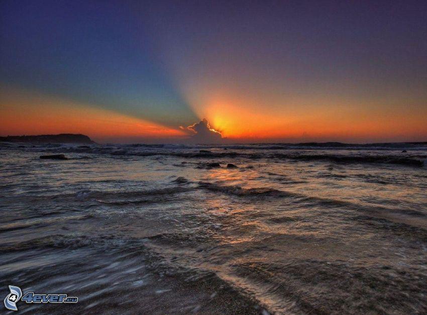 puesta de sol sobre el mar, rayos del sol detrás de las nubes