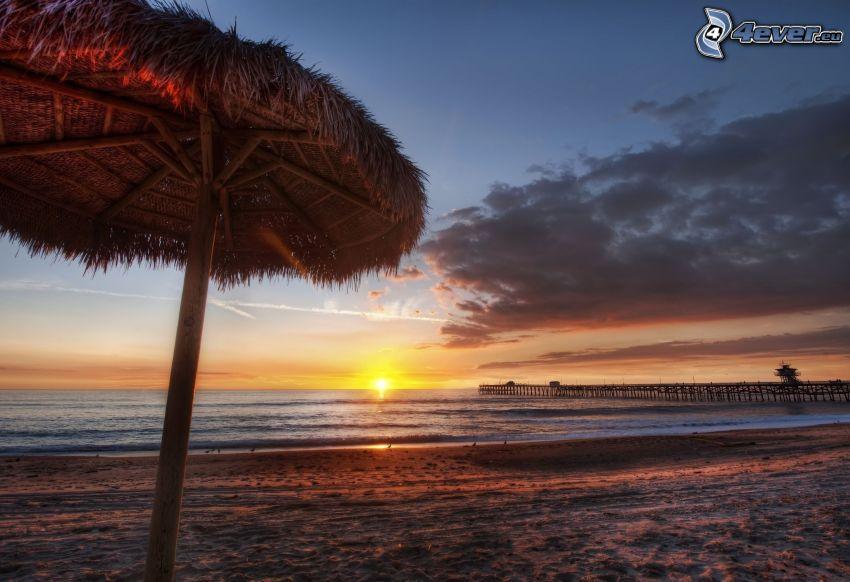 puesta de sol sobre el océano, sombrilla en la playa, muelle