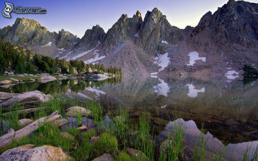 montaña rocosa, hierba en la orilla de un lago