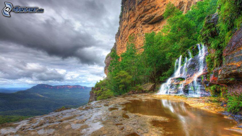 Monte rocoso, cascada, árboles de hoja caduca