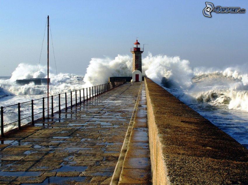 Muelle con faro, mar turbulento, olas en la costa