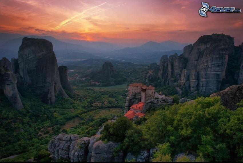 Casas en las rocas, montaña rocosa, Grecia, cielo anaranjado, puesta del sol, marcas de condensación