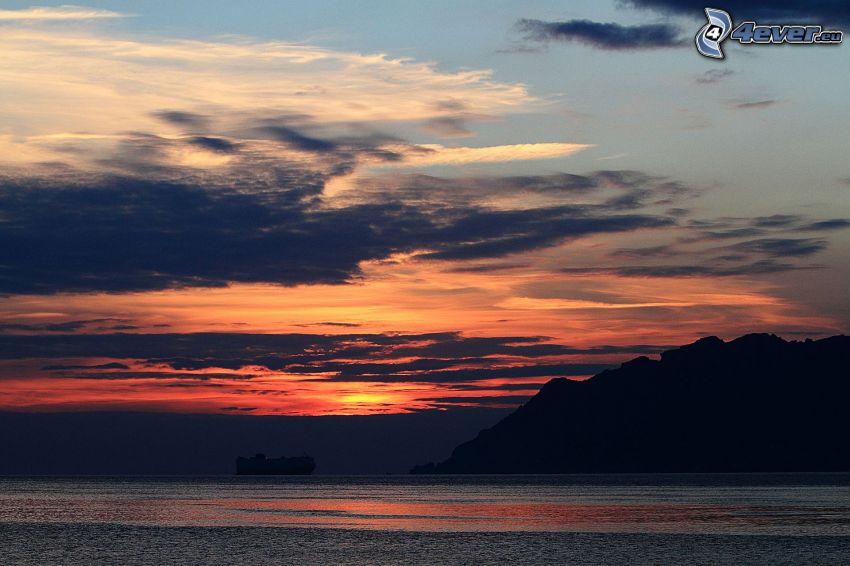 lago, después de la puesta del sol, colina