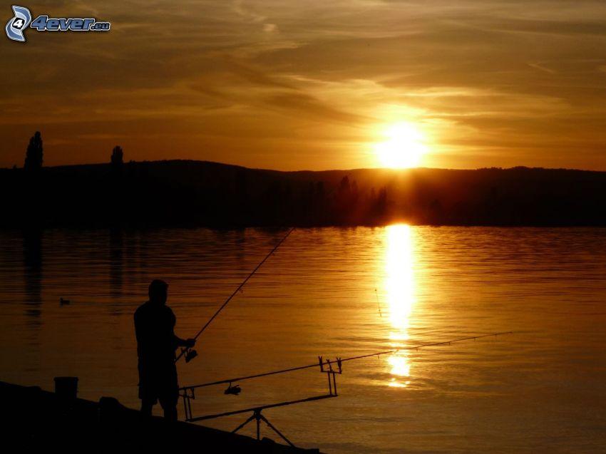 pescador al atardecer, lago