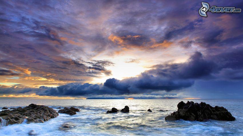 playa rocosa, puesta de sol sobre el mar, nubes oscuras