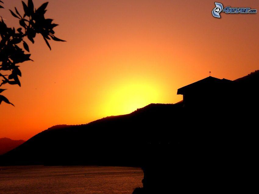 puesta de sol anaranjada, silueta del horizonte, lago