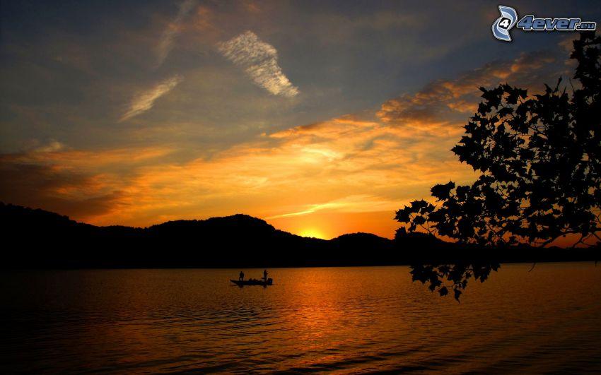 puesta de sol sobre el lago, pescadores