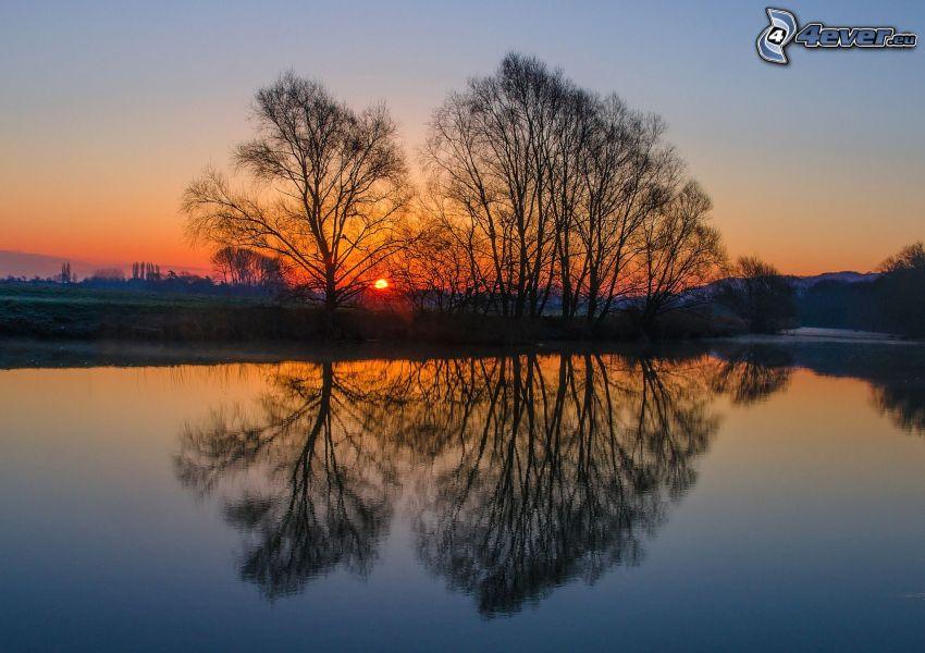 puesta de sol sobre un lago, siluetas de los árboles, reflejo