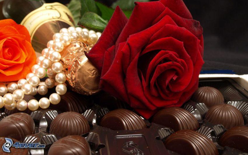 rosa roja, caramelos, champán, collar de perlas