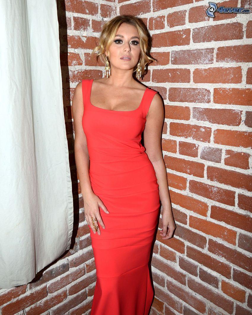 Alexa Vega, vestido rojo, pared de ladrillo