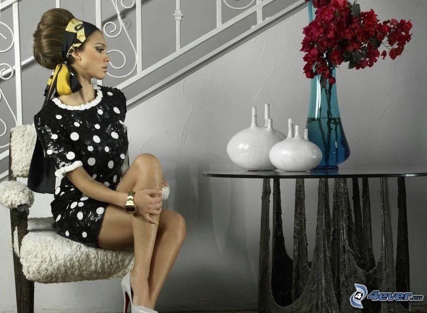 Jessica Alba, vestido punteado, mesa, flores en un florero