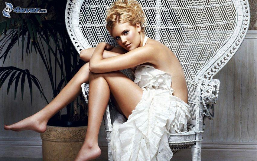 Maggie Grace, vestido blanco, rubia en una silla