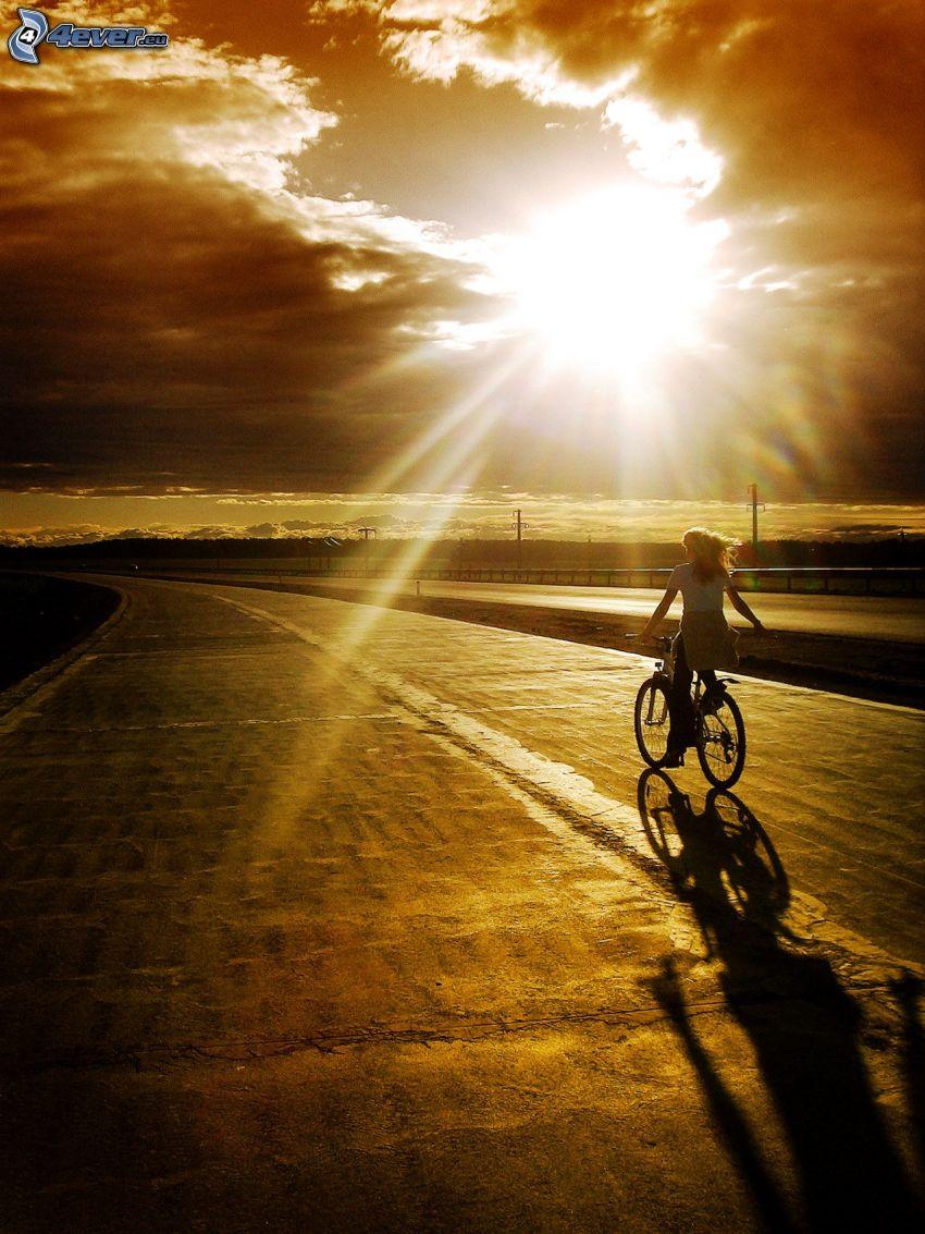 muchacha en la bici, puesta de sol sobre la carretera