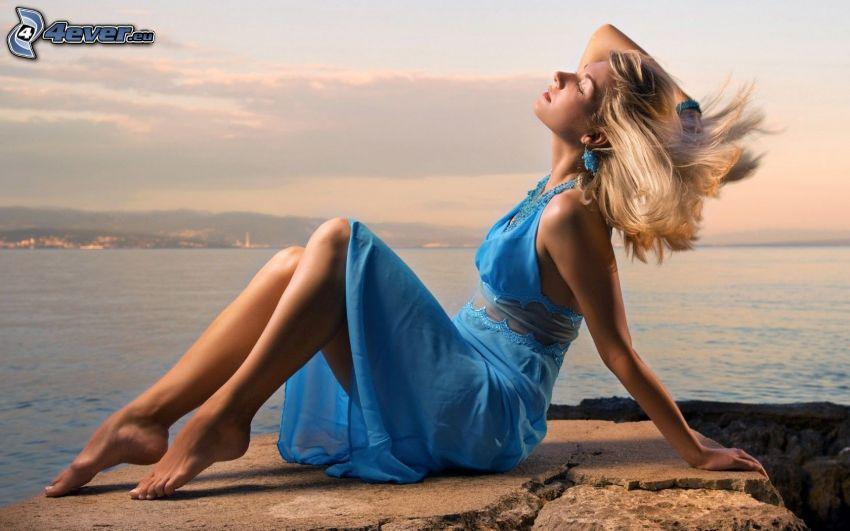 rubia, vestido azul, roca, lago