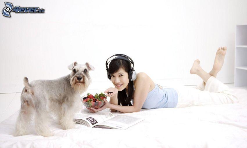 chica con auriculares, perro, libro, mujer en la cama