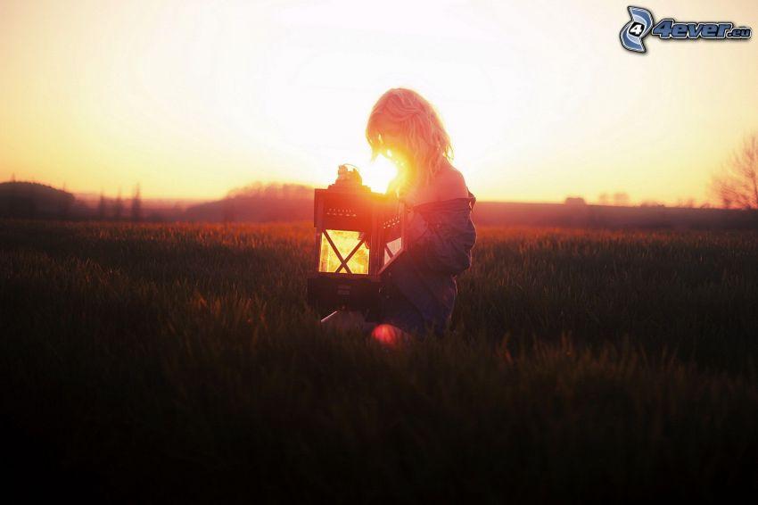 chica en el prado, linterna, puesta de sol en la pradera