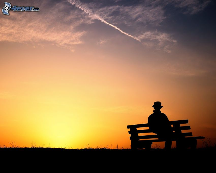 hombre en el banco, silueta del horizonte, puesta de sol detrás del banco