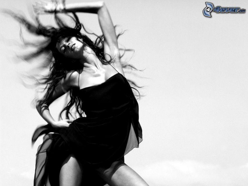 morena, vestido negro, cabello volando