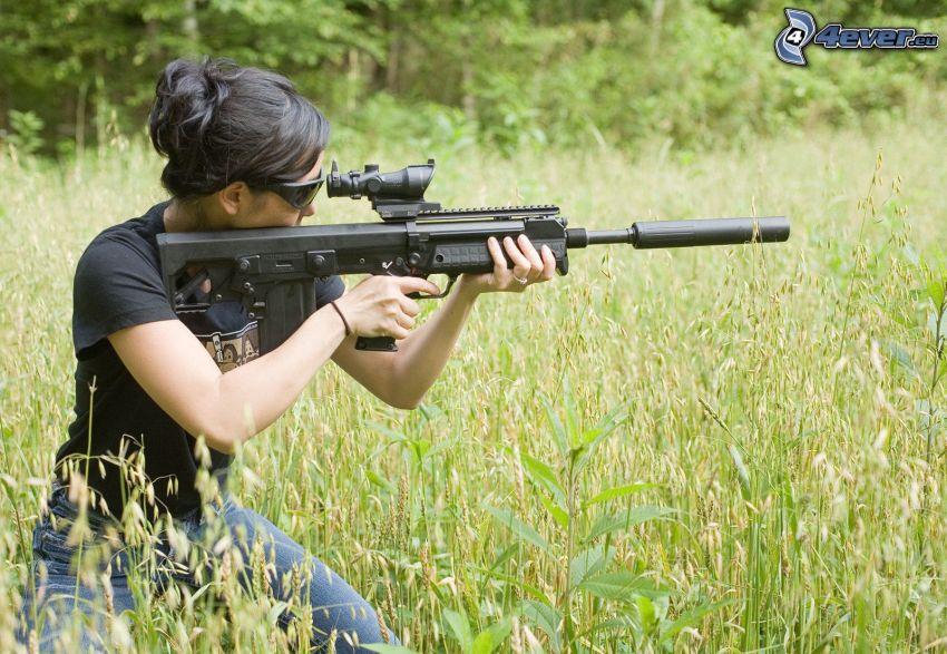 mujer con arma, metralleta, prado