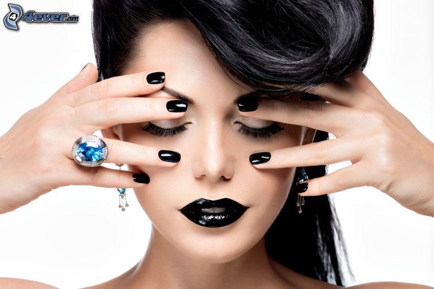 mujer con maquillaje, uñas pintadas, labios negros, anillo
