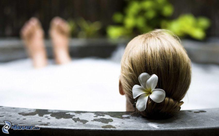 mujer en bañera, flor en el pelo