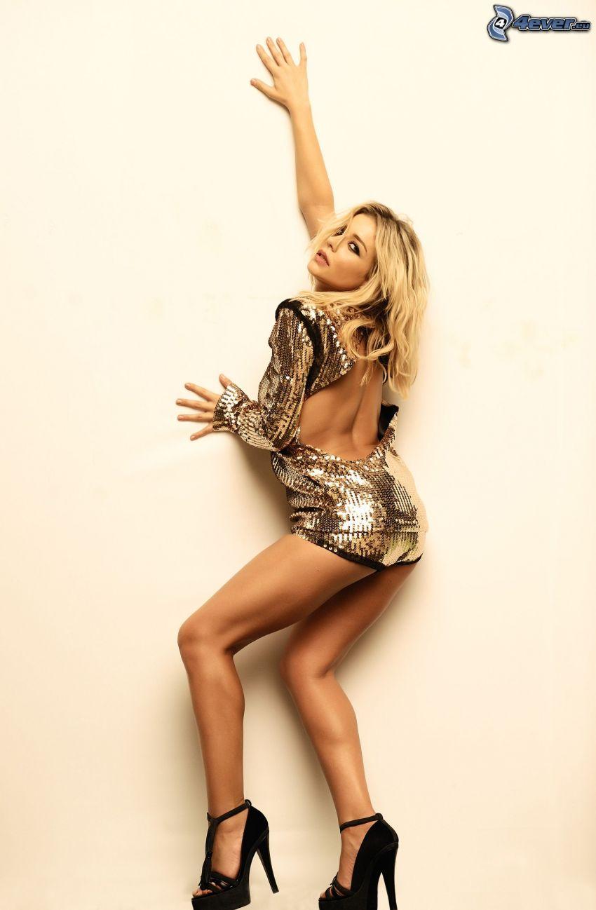 Tina Karol, vestido de oro, zapatos con tacón, pared, espalda