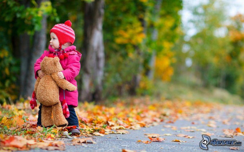niña con un oso peluche, bebé, hojas de colores