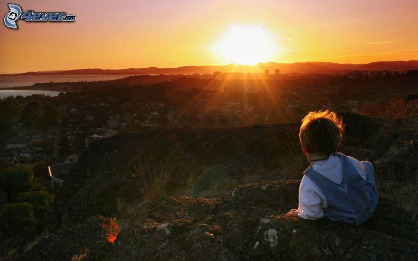 niño, rocas, puesta de sol sobre la ciudad
