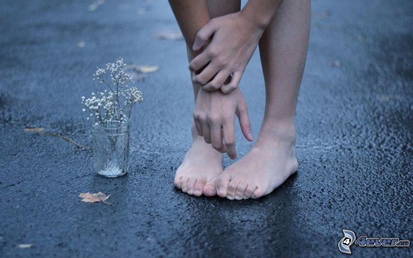 pies, manos, flores del campo en un florero