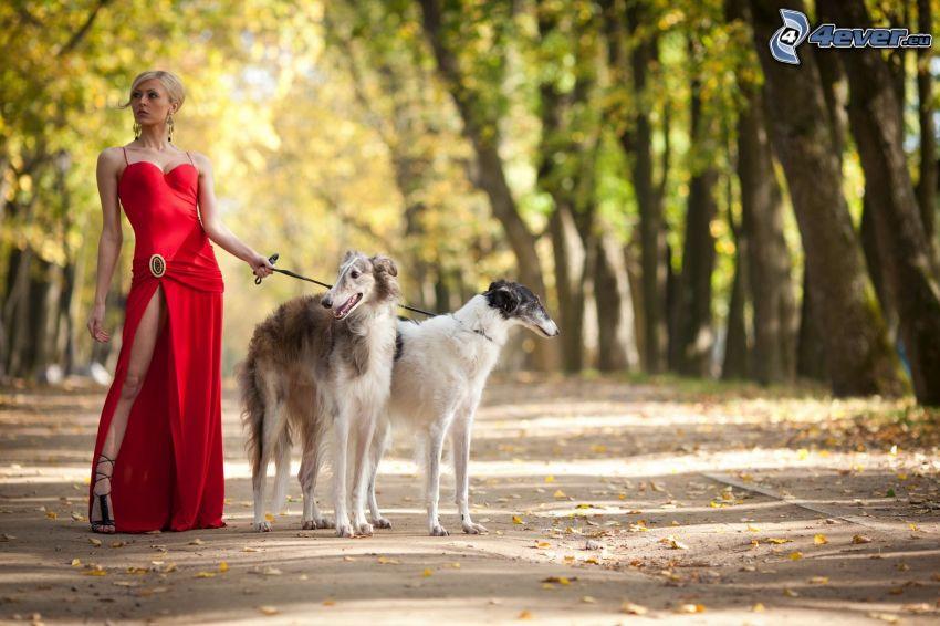 rubia, vestido rojo, dos perros