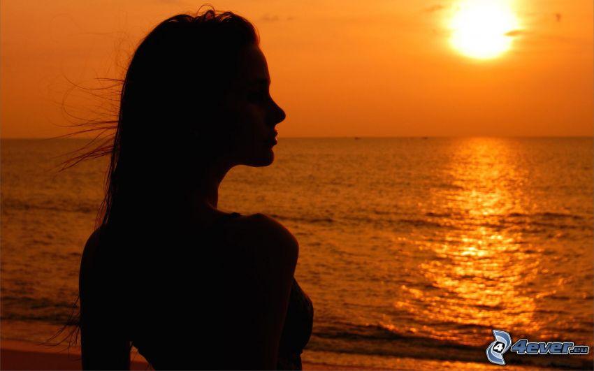 silueta de mujer al atardecer, puesta de sol sobre el mar, cielo anaranjado