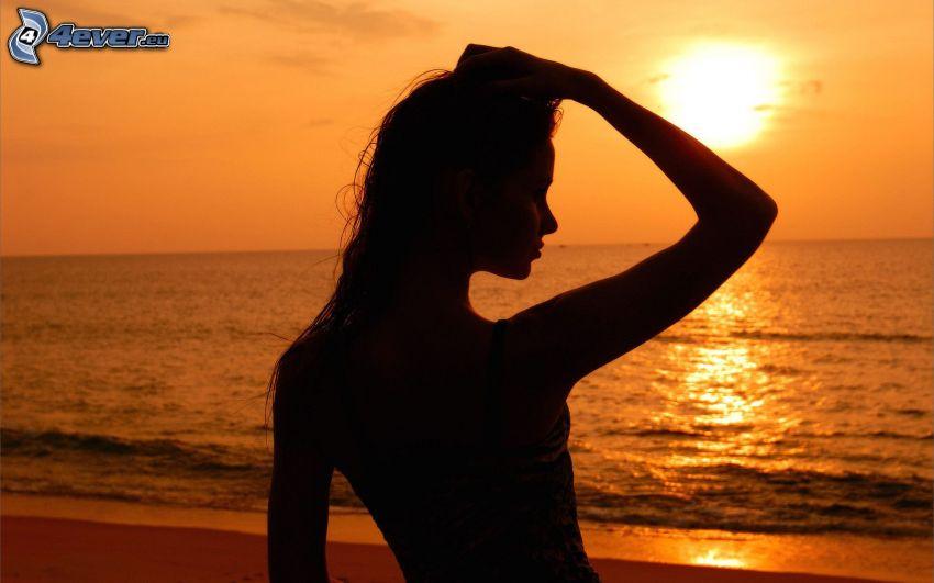 silueta de mujer al atardecer, puesta de sol sobre el océano, cielo anaranjado