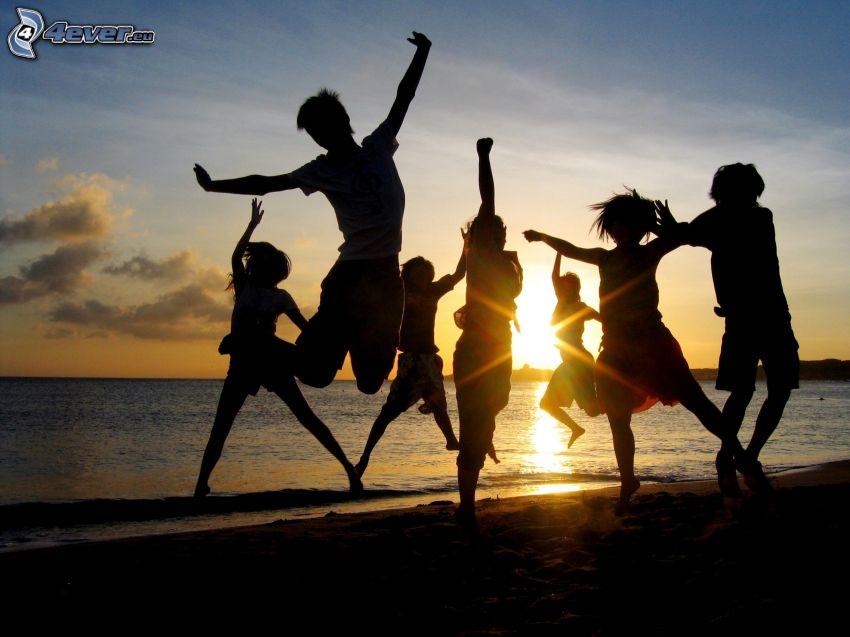 siluetas de personas, puesta de sol sobre el mar, alegría, salto