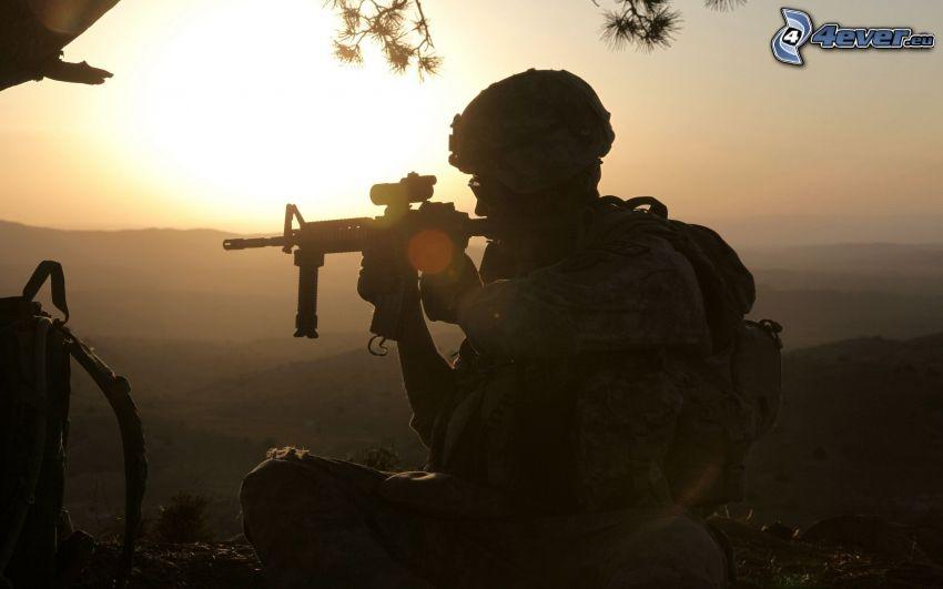 soldado con una pistola, silueta de un hombre, puesta del sol