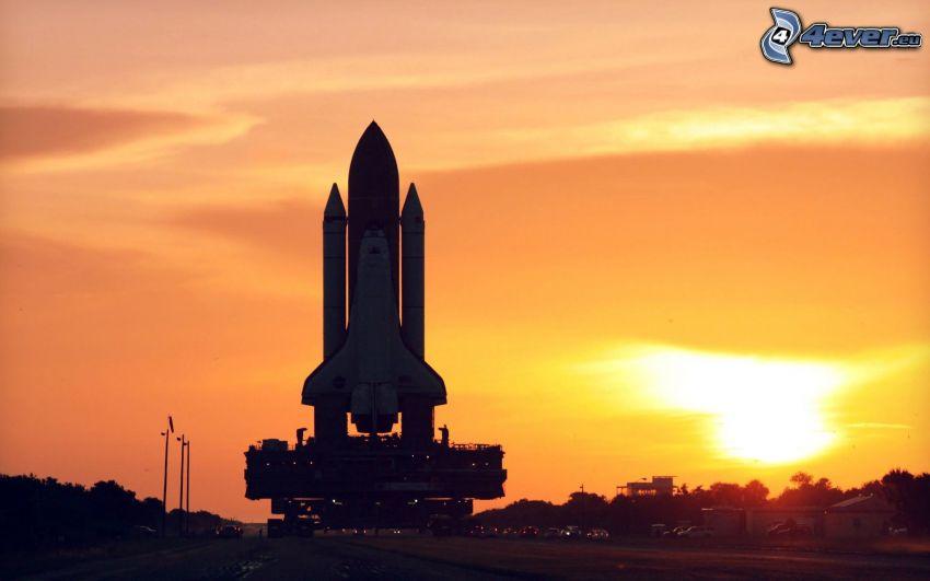 transbordador espacial, rampa de lanzamiento, puesta de sol anaranjada