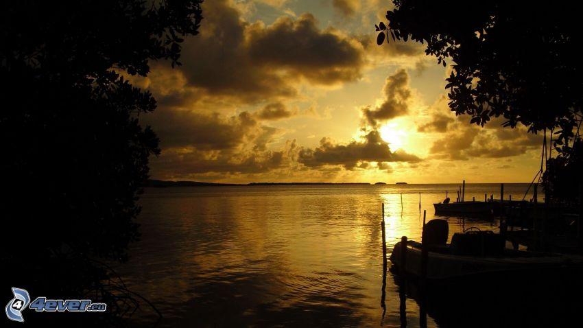 barco en la orilla, puesta de sol sobre el mar