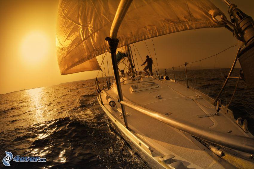 velero, puesta de sol naranja sobre el mar