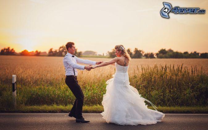 jeunes mariés, coucher du soleil dans le champ, route