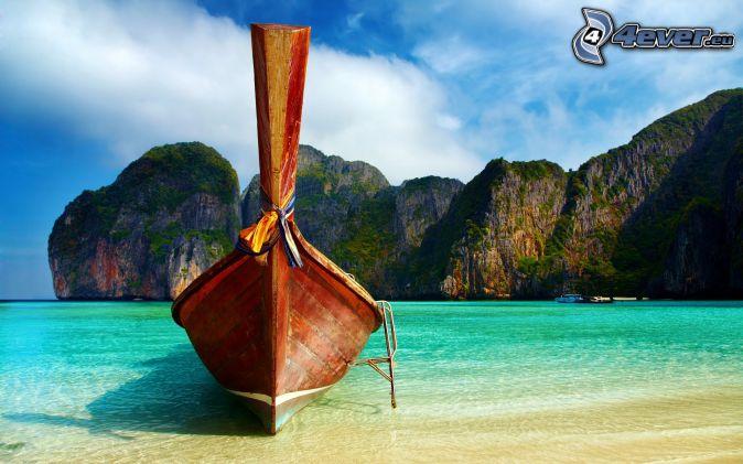 Bateau à quai , la mer d'azur peu profonde , rochers , la thaïlande