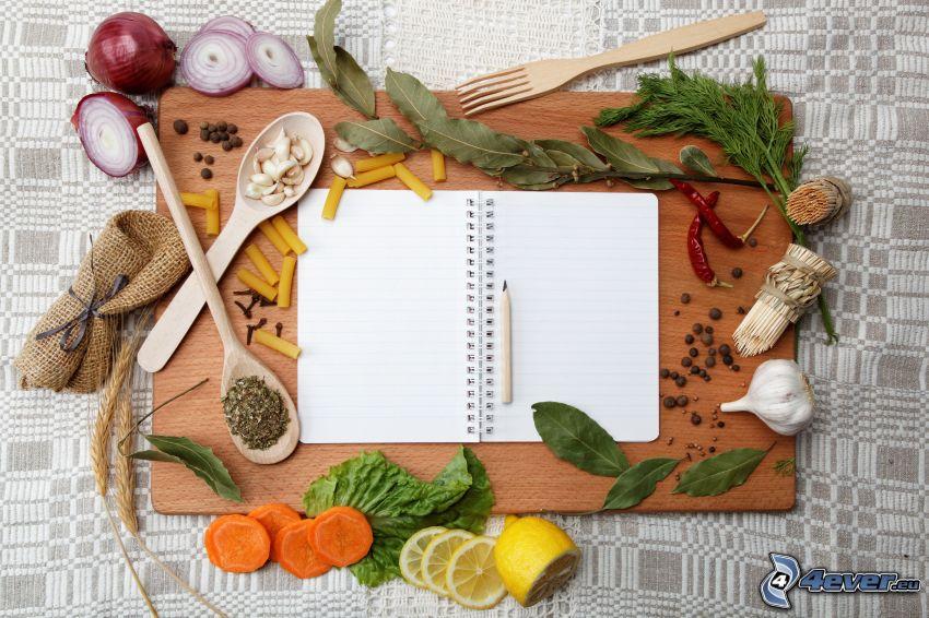 Épices, herbes, oignons, carotte, citron, ail, piments rouges, cahier