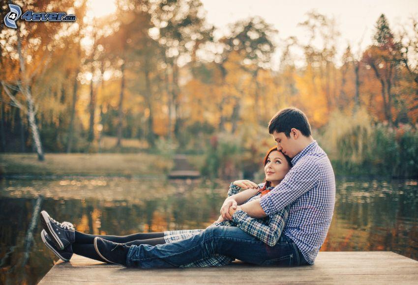 couple au bord du lac, arbres d'automne, jetée