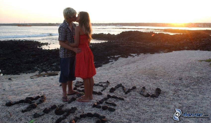 couple près de la mer, baiser, couchage de soleil à la mer