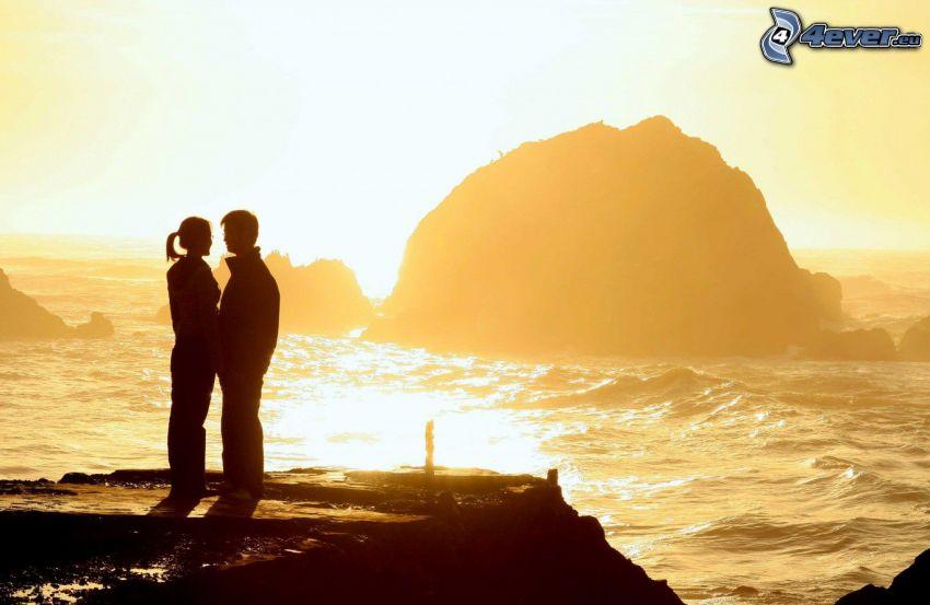 couple près de la mer, falaise, roche dans la mer, coucher du soleil