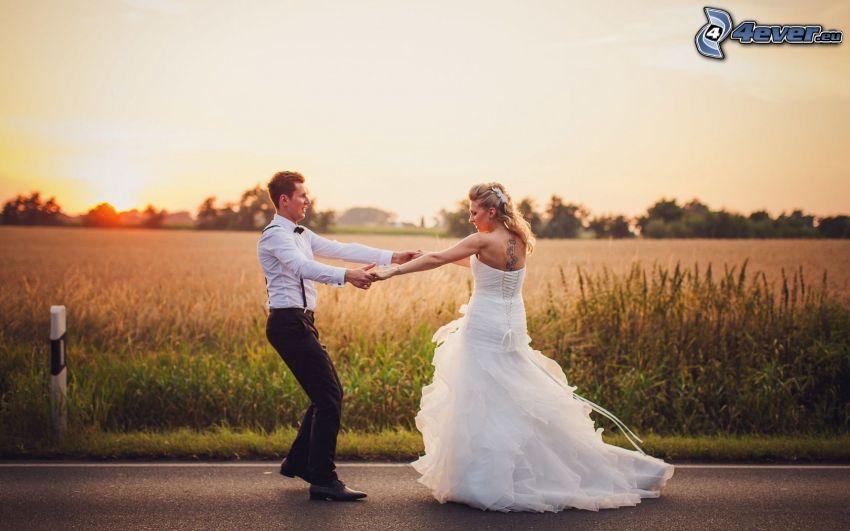 jeunes mariés, danse, coucher du soleil dans le champ, route