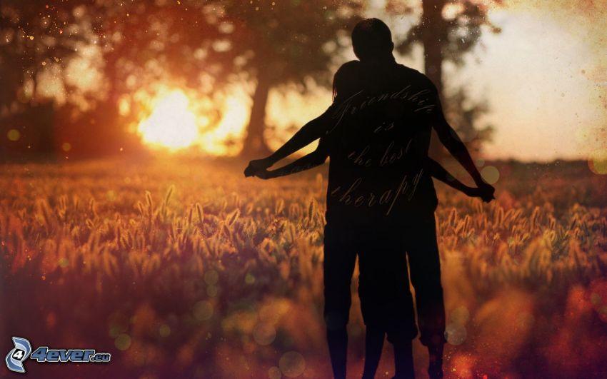 silhouette du couple, grain, coucher du soleil dans le champ