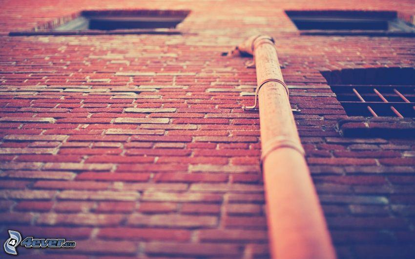 pipe, mur de briques