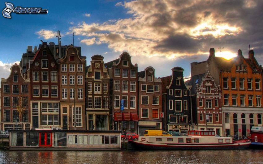 Amsterdam, fossé, navires, maisons, couchage de soleil dans la ville, nuages sombres