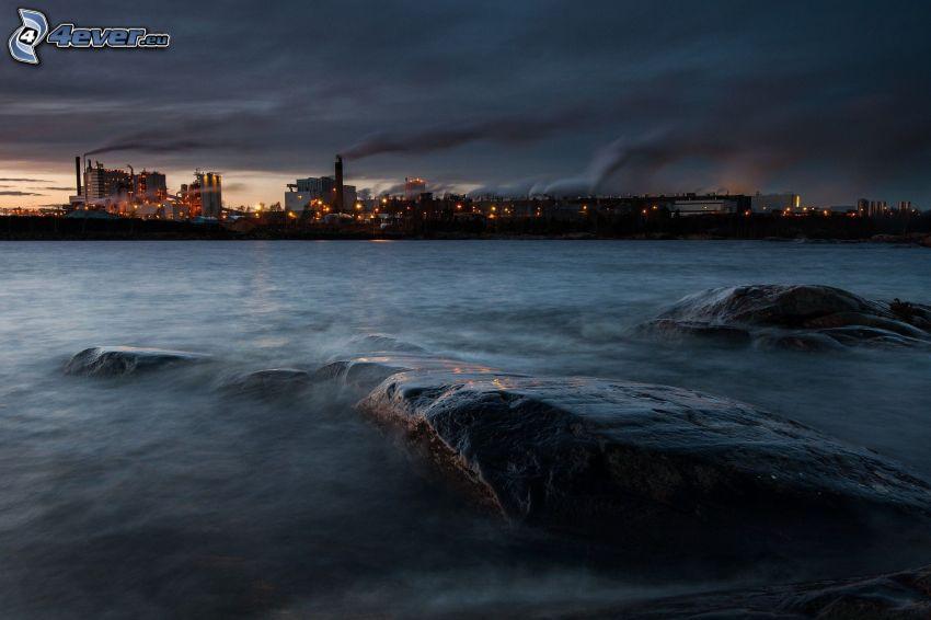 ville dans la nuit, rochers, rivière, maisons