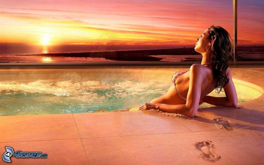 femme dans la piscine, couchage de soleil sur la mer, empreintes dans le sable
