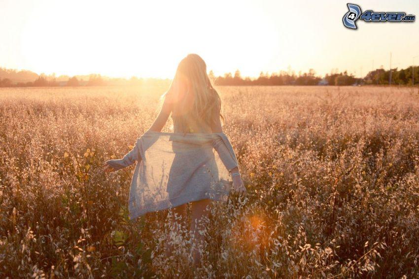 la fille sur le champ, coucher du soleil, femme mince